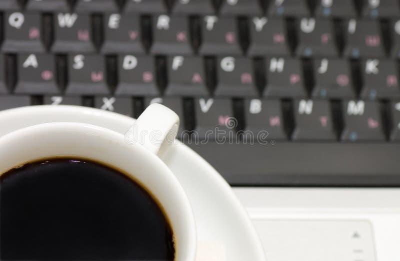 Cuvette de café sur l'ordinateur portatif image stock