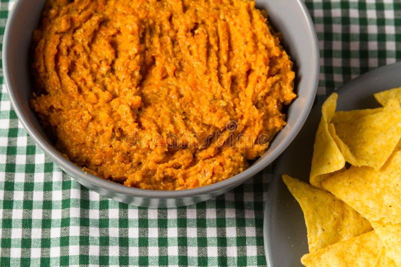 Cuvette de houmous de carotte avec des puces de tortilla photos stock