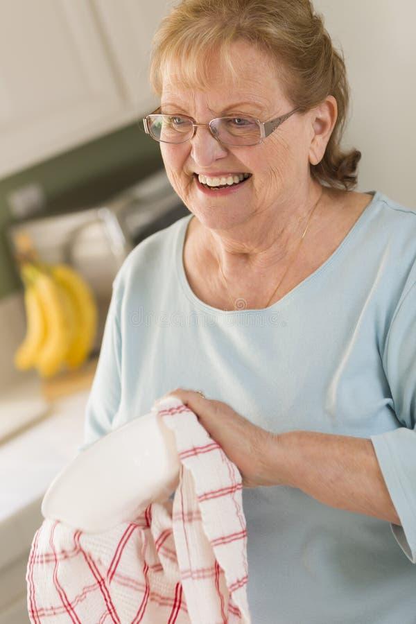 Cuvette de séchage de femme adulte supérieure à l'évier dans la cuisine images libres de droits