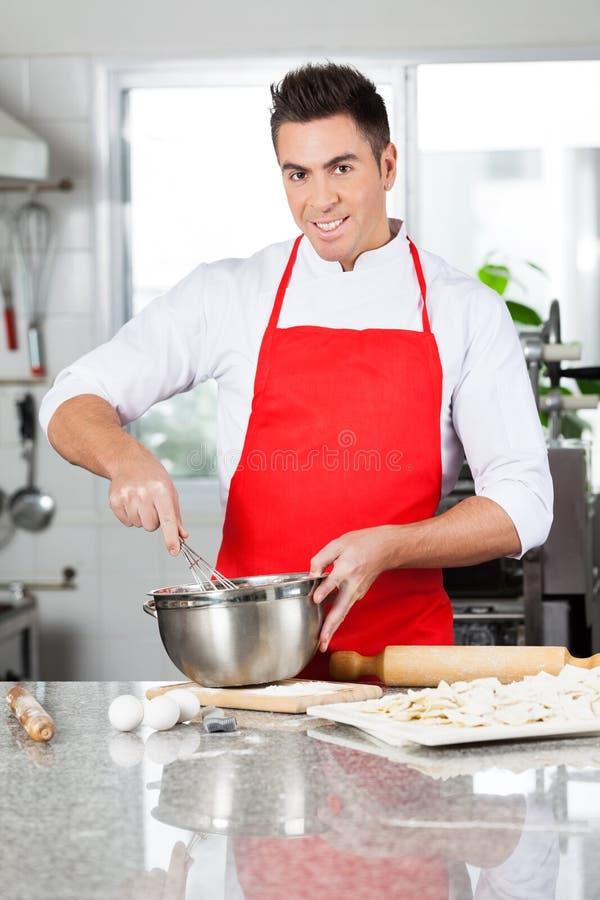 Cuvette de sourire de Mixing Batter In de chef à préparer photographie stock