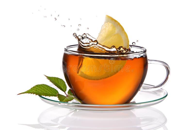 Cuvette de thé avec le citron et l'éclaboussure image stock