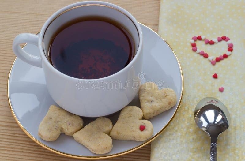 Cuvette de thé de rooibos avec les biscuits en forme de coeur pour le Saint Valentin image libre de droits