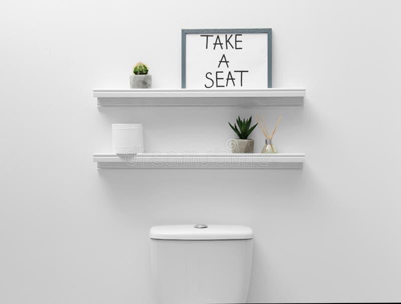 Cuvette des toilettes, éléments de décor et signe drôle près du mur blanc image libre de droits