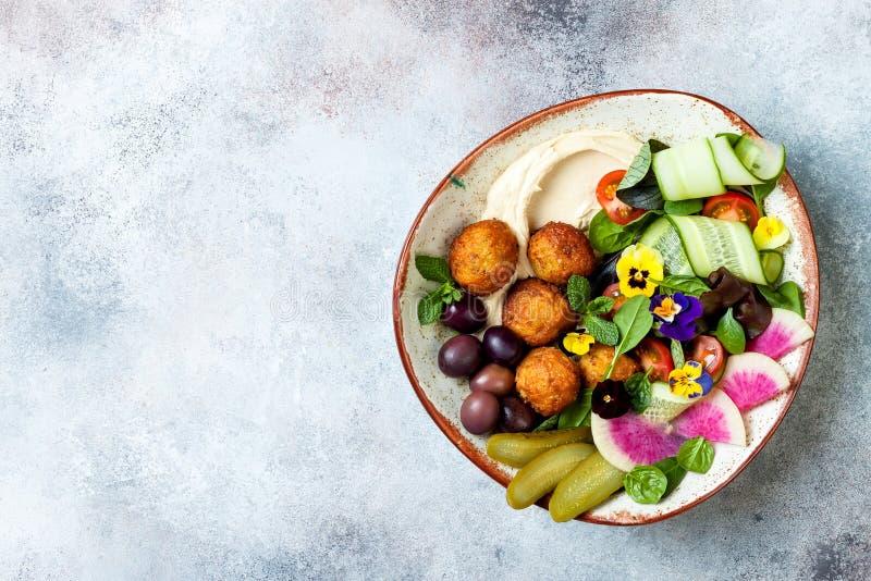 Cuvette du Moyen-Orient de Bouddha de déjeuner avec le houmous, le falafel, la tomate et la salade de verts, les olives, les con photographie stock