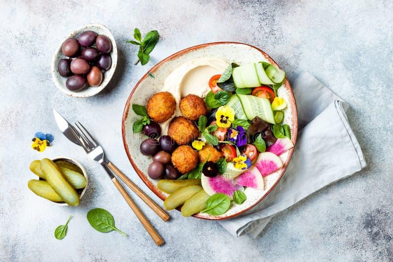 Cuvette du Moyen-Orient de Bouddha de déjeuner avec le houmous, le falafel, la tomate et la salade de verts, les olives, les con images libres de droits
