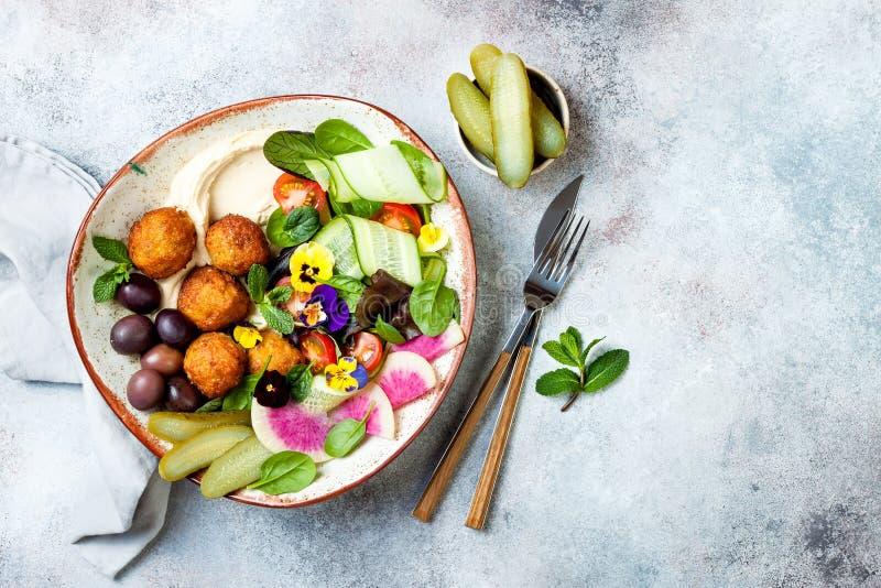 Cuvette du Moyen-Orient de Bouddha de déjeuner avec le houmous, le falafel, la tomate et la salade de verts, les olives, les con image libre de droits