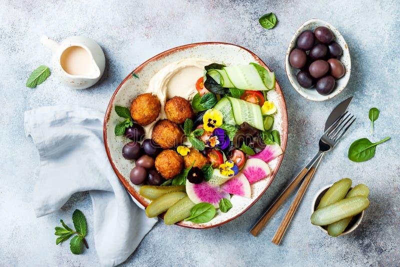 Cuvette du Moyen-Orient de Bouddha de déjeuner avec le houmous, le falafel, la tomate et la salade de verts, les olives, les con photos libres de droits