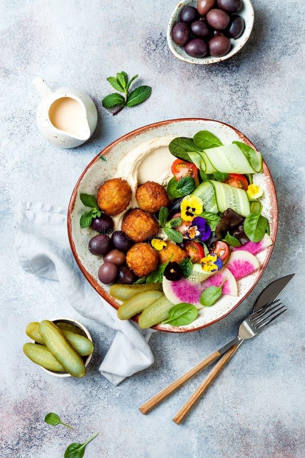 Cuvette du Moyen-Orient de Bouddha de déjeuner avec le houmous, le falafel, la tomate et la salade de verts, les olives, les con images stock