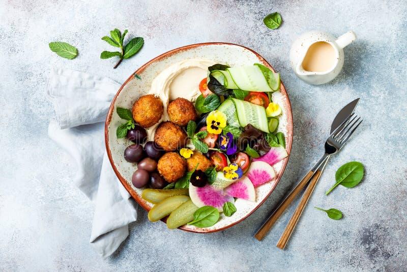 Cuvette du Moyen-Orient de Bouddha de déjeuner avec le houmous, le falafel, la tomate et la salade de verts, les olives, les con image stock