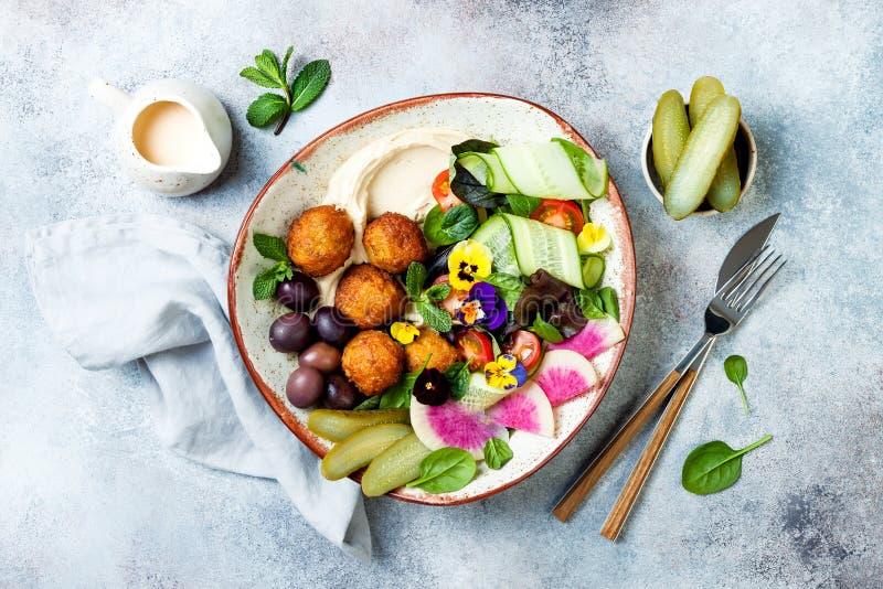 Cuvette du Moyen-Orient de Bouddha de déjeuner avec le houmous, le falafel, la tomate et la salade de verts, les olives, les con photo libre de droits