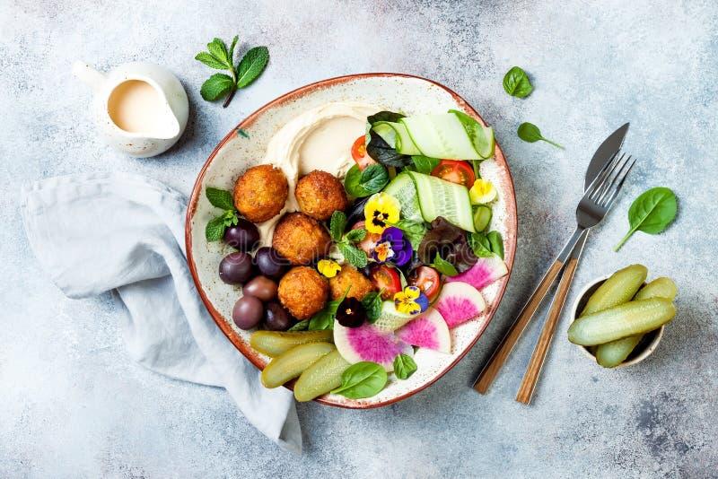 Cuvette du Moyen-Orient de Bouddha de déjeuner avec le houmous, le falafel, la tomate et la salade de verts, les olives, les con photographie stock libre de droits