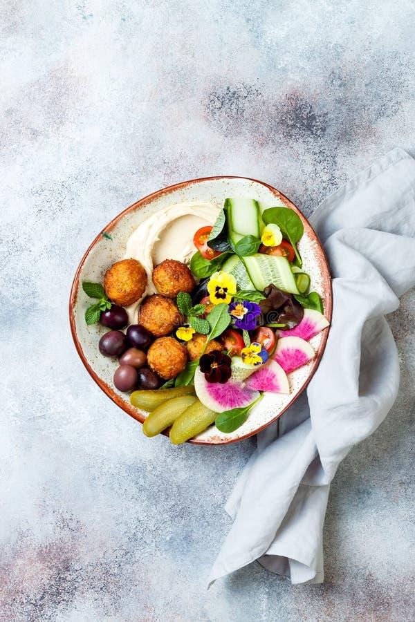 Cuvette du Moyen-Orient de Bouddha de déjeuner avec le houmous, le falafel, la tomate et la salade de verts, les olives, les con photo stock