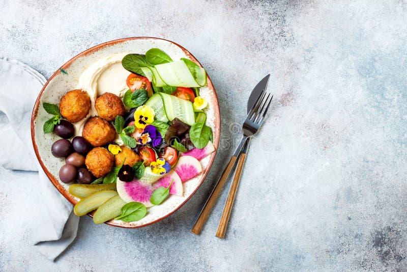 Cuvette du Moyen-Orient de Bouddha de déjeuner avec le houmous, le falafel, la tomate et la salade de verts, les olives, les con photos stock