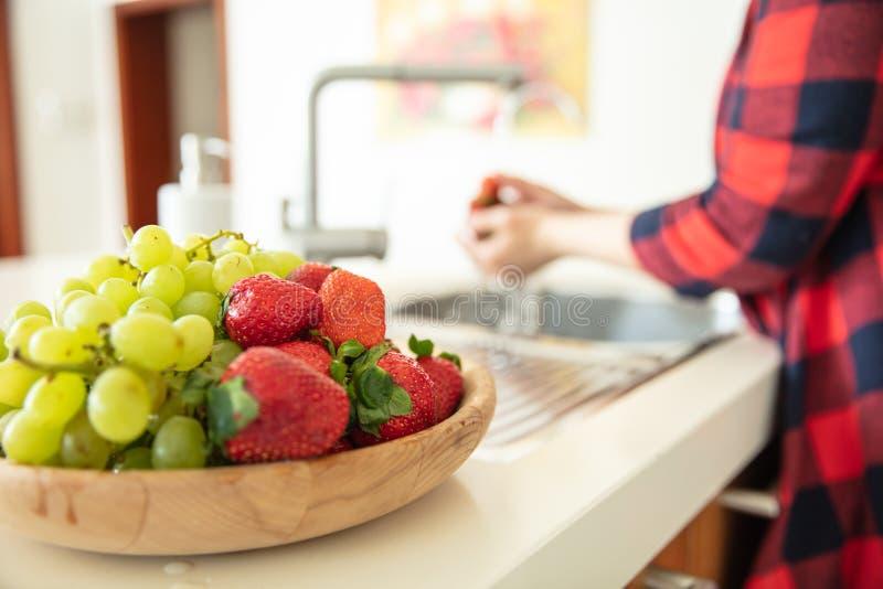 Cuvette en bois avec des raisins et les fraises verts photo libre de droits