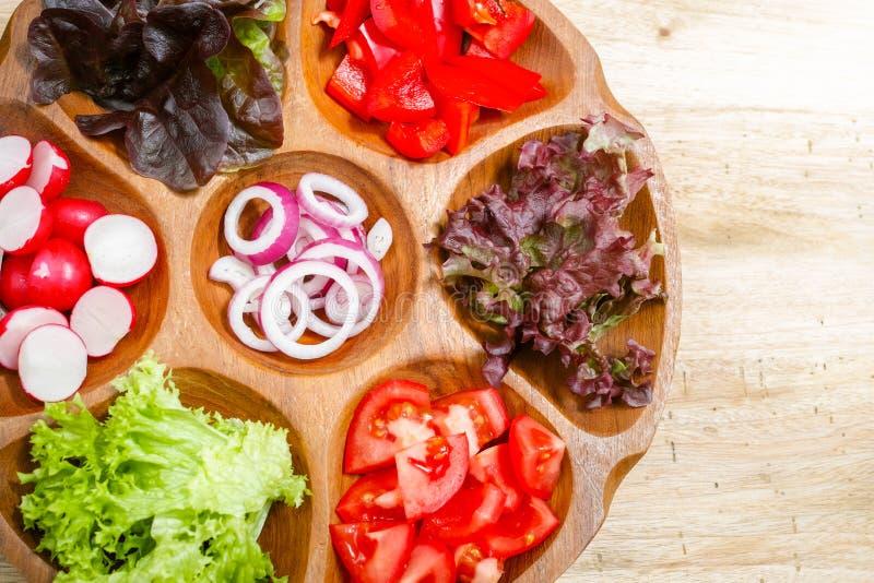 Cuvette en bois avec les ingrédients mélangés pour la salade de légume frais photographie stock libre de droits