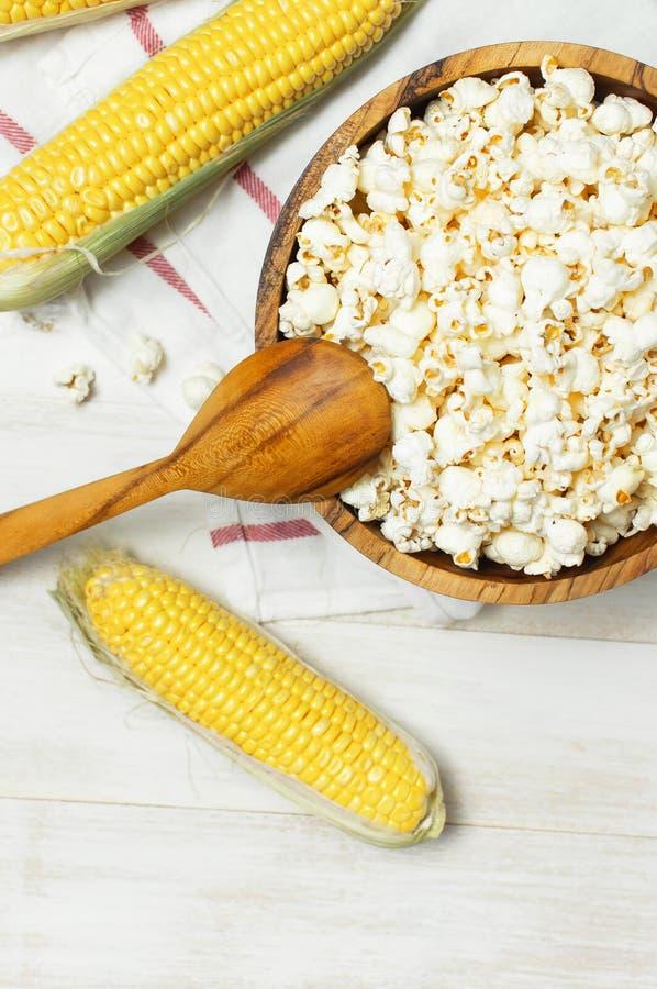 Cuvette en bois de Brown avec le maïs éclaté traditionnel délicieux, le maïs frais et une cuillère sur un fond en bois clair Vue  image stock