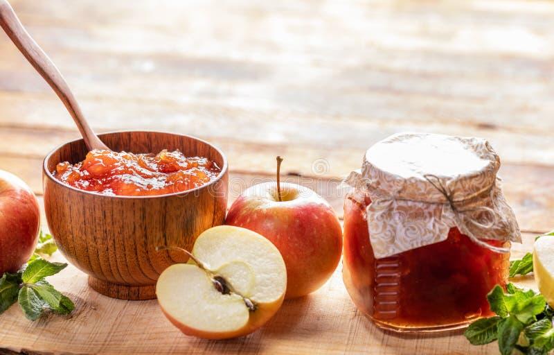 Cuvette en bois et pot en verre avec de la confiture de pomme et pommes et menthe verte sur le fond en bois photos libres de droits