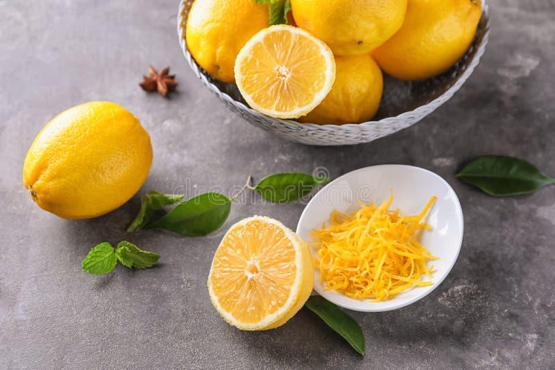 Cuvette en osier avec les citrons mûrs et entrain frais sur la table grise photographie stock