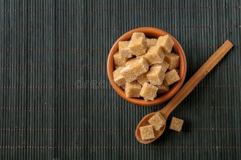Cuvette et cuillère avec du sucre de canne brun sur la table foncée images stock