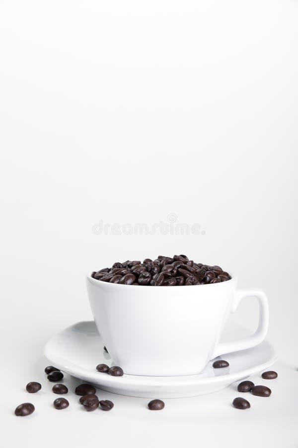 Cuvette et haricots de caf? sur un fond blanc image stock