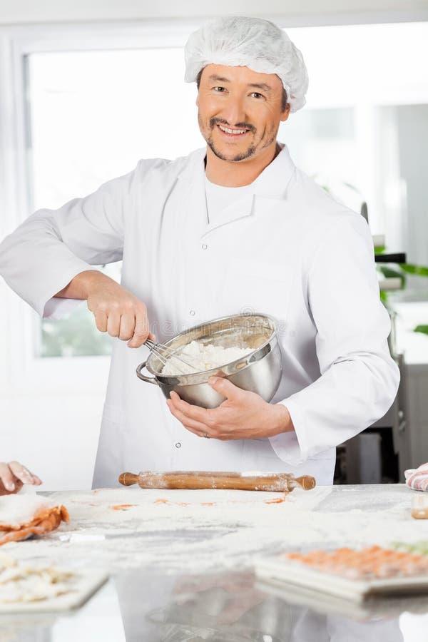Cuvette heureuse de Mixing Batter In de chef à préparer image stock