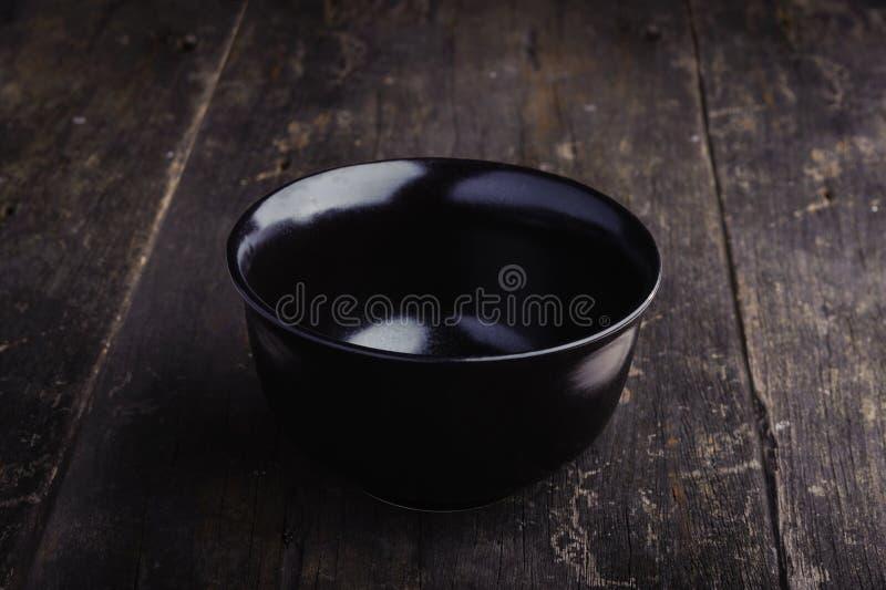 Cuvette noire vide de porcelaine sur le fond en bois grunge images stock