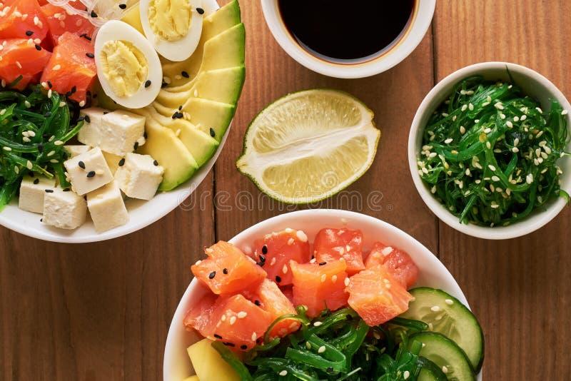 Cuvette organique crue de poussée avec du riz, avocat, saumon, mangue, concombres, salade de chuka, oeufs de caille, oignons doux image libre de droits