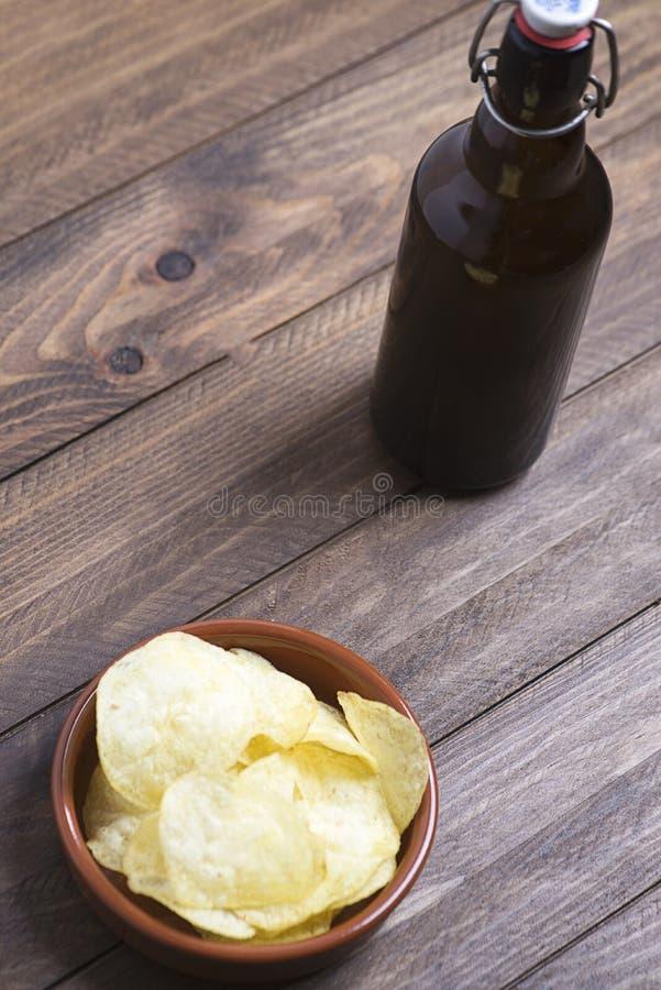 Cuvette rustique avec des puces à côté d'une bière sur la table en bois photos libres de droits