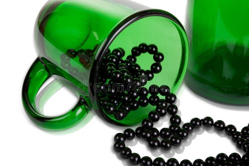Cuvette verte, bouteille en verre et programmes noirs images stock