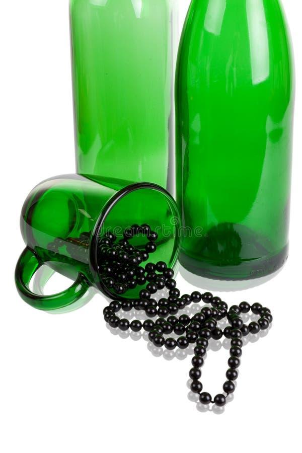 Cuvette verte, bouteille en verre et programmes noirs photos stock