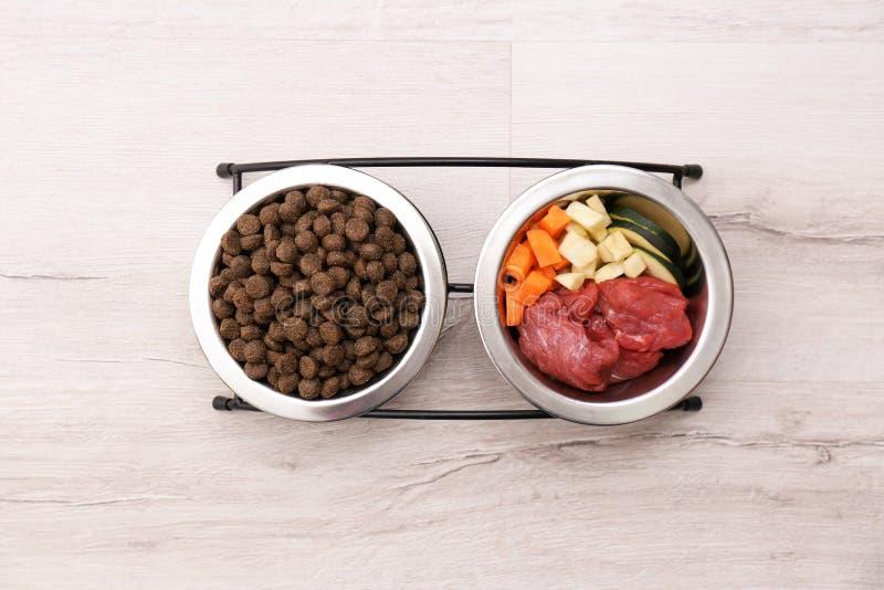 Cuvettes avec les aliments pour chiens secs et naturels dessus photographie stock libre de droits