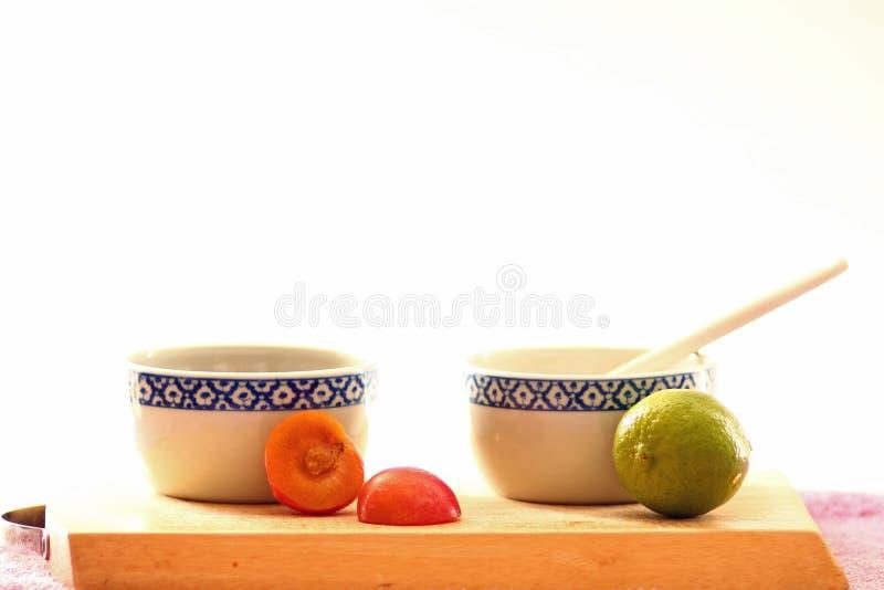 Cuvettes blanches et bleues avec des écrous et des graines sur le conseil en bois images stock