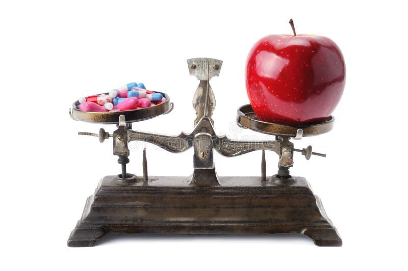 Cuvettes d'échelles, de pomme et de pilules photographie stock libre de droits