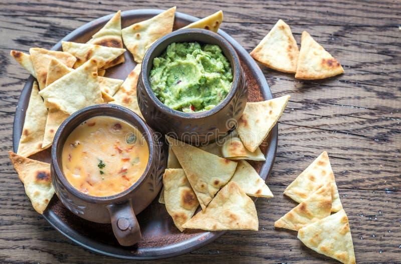 Cuvettes de guacamole et de queso avec des puces de tortilla photographie stock