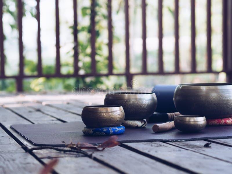Cuvettes de tapis et de chant de yoga pour le maditation sur le bois en nature photographie stock libre de droits