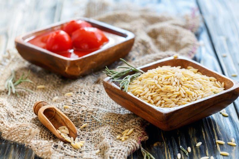 Cuvettes en bois avec des pâtes d'orzo et des tomates en boîte images libres de droits