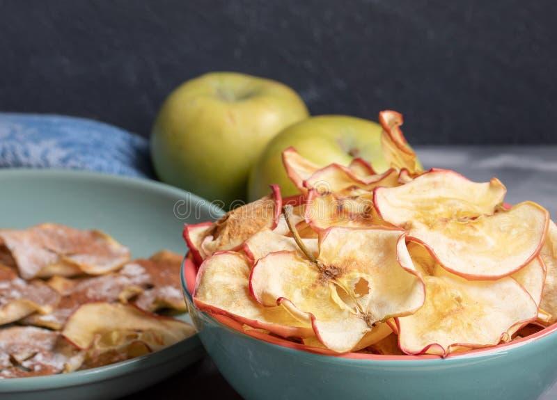 Cuvettes en c?ramique en gros plan avec les puces saines de pomme et pommes enti?res sur le fond gris-fonc? photo libre de droits