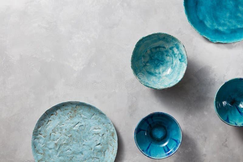 Cuvettes et plats bleus de porcelaine sur une table de marbre grise Plats faits main de vintage en céramique multicolore photo libre de droits