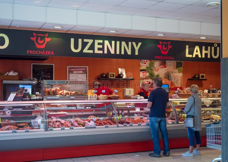 Cvikov, CZECH REPUBLIC - MAY 24, 2019: Frontal view of butcher shop in penny market with female butcher showing meat to royalty free stock photo