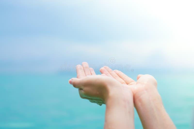 CWoman一起递地方象祈祷从在日落海滩前面的自然 免版税图库摄影