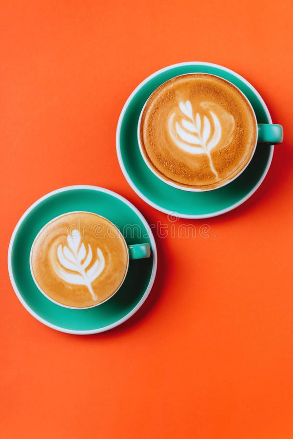 Cyan coffee cups over orange background. Cyan cappuccino coffee cups over orange background. Top view flat lay with copy space stock photo