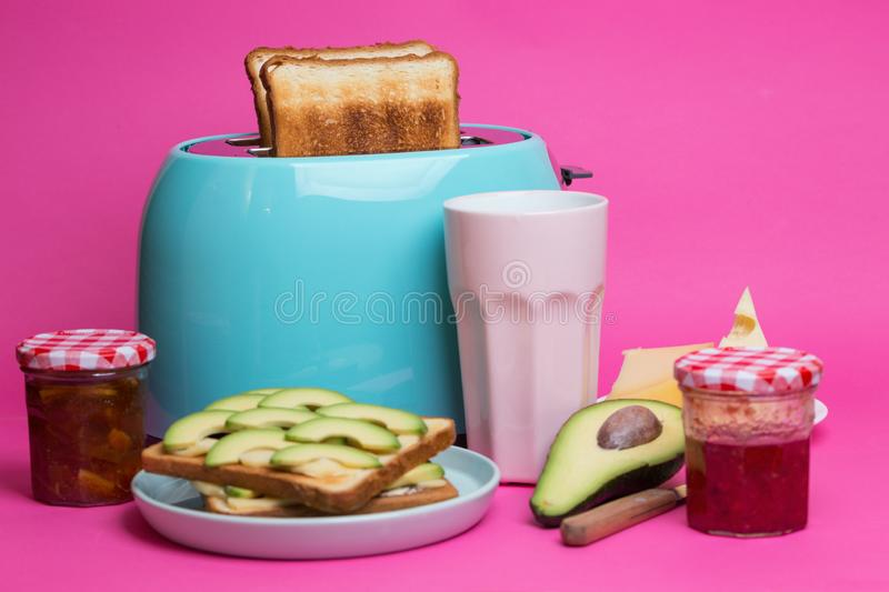 Cyan color toaster on a pink background. Bright, fun breakfast. cyan color toaster on a pink background royalty free stock image