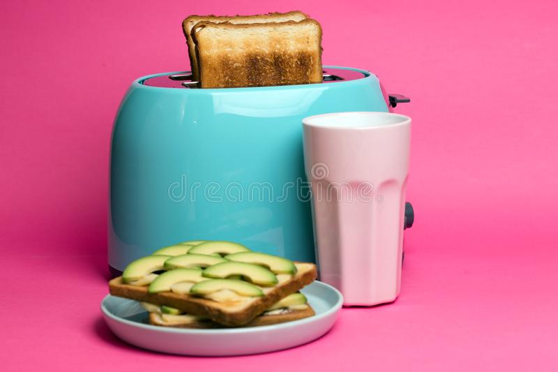 Cyan color toaster on a  pink background. Bright, fun breakfast. cyan color toaster on a  pink background royalty free stock photo
