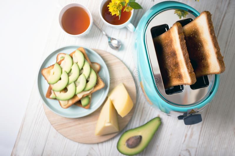 Cyan color toaster on a wooden background. Bright, fun breakfast. cyan color toaster on a wooden background stock photography
