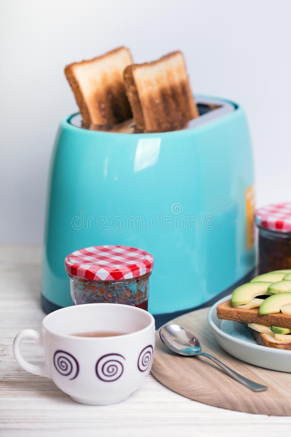 Cyan color toaster on a wooden background. Bright, fun breakfast. cyan color toaster on a wooden background royalty free stock photography