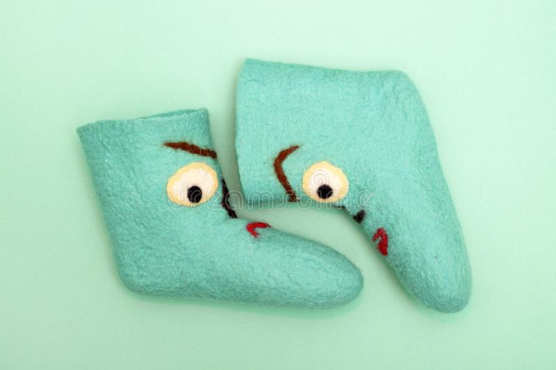 Cyan felt socks with a pattern. On a turquoise background stock photos