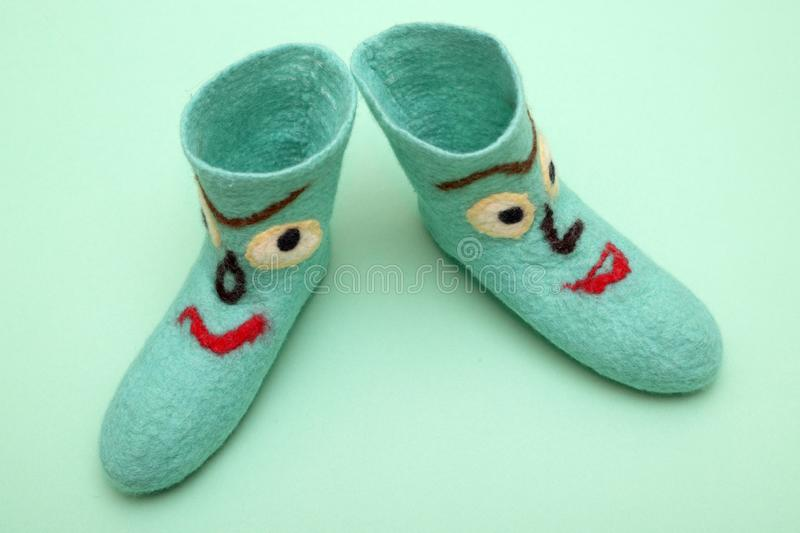 Cyan felt socks with a pattern. On a turquoise background royalty free stock photos