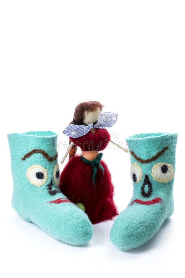 Cyan felt socks with a pattern. On a white background with a felted doll royalty free stock photo
