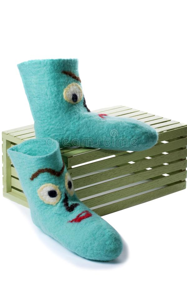 Cyan felt socks with a pattern. On a white background on a wooden box royalty free stock photography