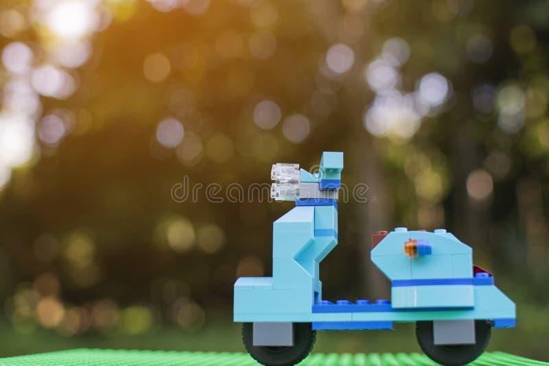 Cyan motocyklu cegieł zabawki plastikowy stojak na zielonym klingerytu talerzu z rozmytym drzewnym tłem obraz royalty free